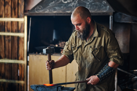Blacksmith working in the forge. Manufacture of parts  from molten metal, using the hammer and anvil. Archivio Fotografico