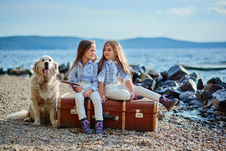Two little twin sisters on a walk with dog