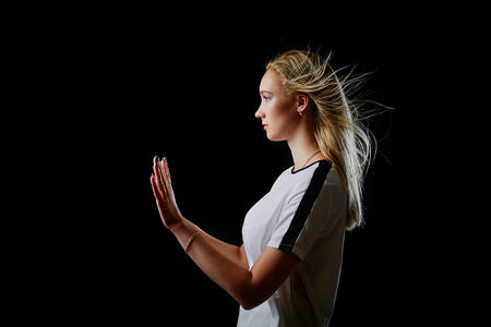 Portrait in profile of a beautiful blonde girl in a sports t-shirt on a black background