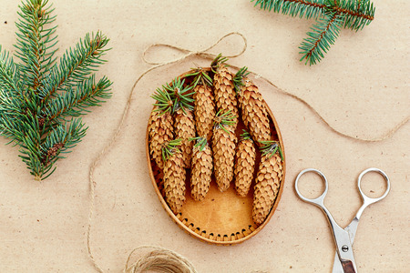 Handmade Christmas gifts, and everything necessary for them, on the Background of Kraft paper, scissors, pine cones and  jute cord. The view from the top.