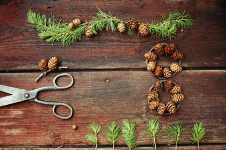 Christmas background on old wooden boards with decorative element in the shape of a figure eight, antique scissors and cones of larch