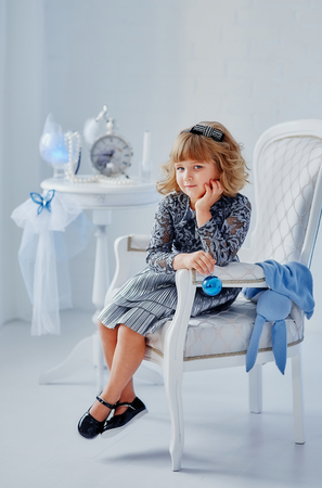 little girl sitting in a luxurious chair in a bright room Stock Photo