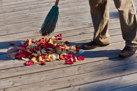 Multicolored rose petals are swept with a broom after the wedding ceremony Banco de Imagens