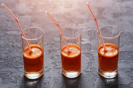 Glasses with freshly squeezed carrot juice on a dark stone background Zdjęcie Seryjne