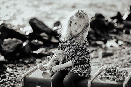 Sad child with a toy sitting on a vintage suitcase on the beach