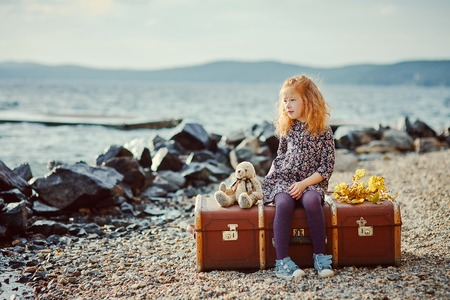A little sad girl with a toy sitting on a large suitcase near the sea. Looks into the distance