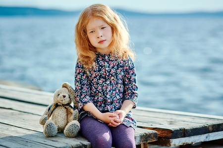 Lonely girl with a toy sitting on a pontoon near the water