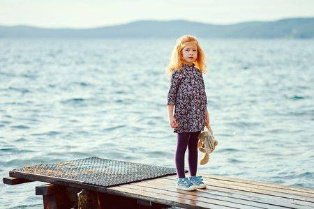 A lonely girl with a plush Bunny is standing on the pier and looks into the distance at the sea Stock Photo