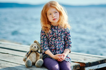Sad child with a toy sitting on the pier near the water.