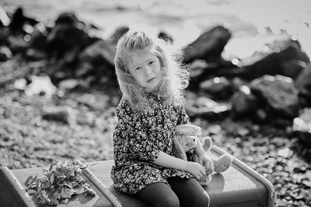 Sad child with a toy sitting on a vintage suitcase on the beach.