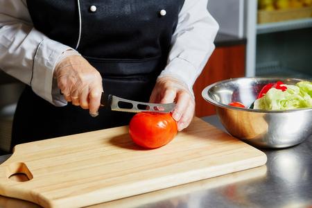 Chef cutting tomato on cutting board. Banco de Imagens