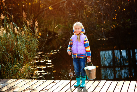 Lonely little child fishing from wooden dock on lake.