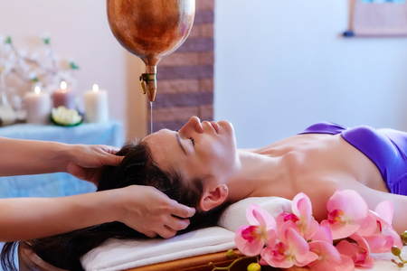 Young woman having pouring oil massage  spa treatment. Shirodhar Stock Photo