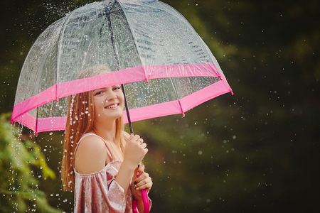A teenage girl hid from the rain under an umbrella while walking through the park.She laughs and smiles, rejoices in the warm and rainy weather Standard-Bild
