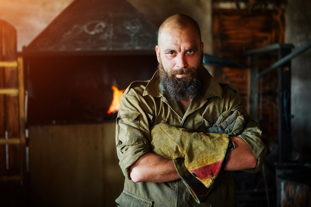 Portrait of a brutal, confident blacksmith, a man with a beard. Standing in the workshop, folding his arms over his chest.