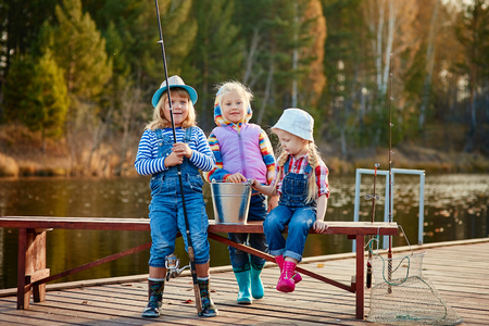 Children fishing with fishing rods. Warm autumn day. Fishing on a wooden pontoon.
