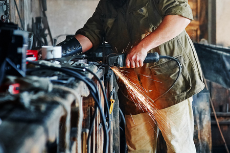 worker cuts detail angle grinder in the workshop and throws sparks.
