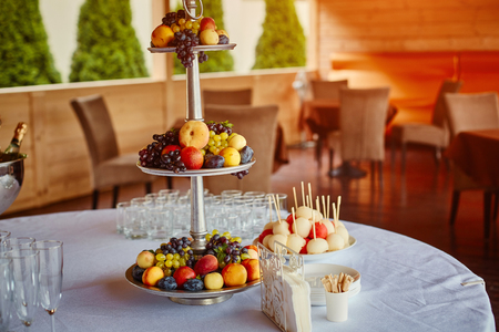 Fourchette buffet table for guests at the celebration, candy bar, fruit,  champagne.