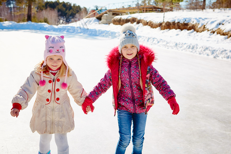 Happy children ice skating on an ice rink outdoors. Sport and a healthy lifestyle. Funny kids, they are sisters and girlfriends.