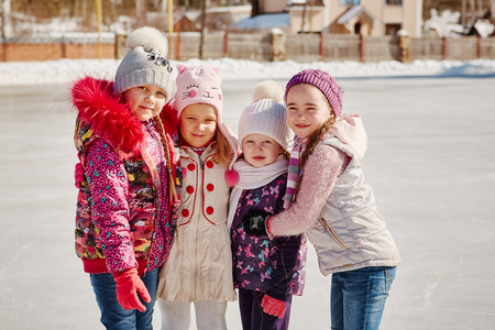 Four little happy girls are skating. They have fun with friends