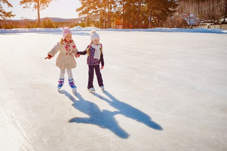 Two little girls hold hands and skate. Space for text.