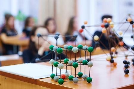 Des écoliers dans une classe de sciences avec un modèle moléculaire. Image de fond avec flou artistique. Notion d'éducation. Banque d'images