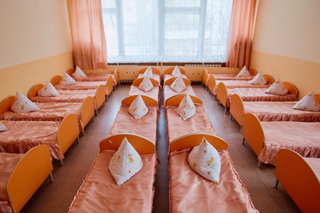 Beds and cots in brightly colored dormitory of a nursery.A lot of childrens cots