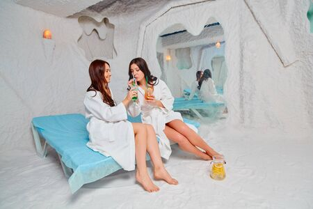 Two young women relax and drink a vitamin drink. Applying salt therapy in the Spa