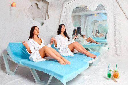Two young women meditate in the salt room. Stock Photo
