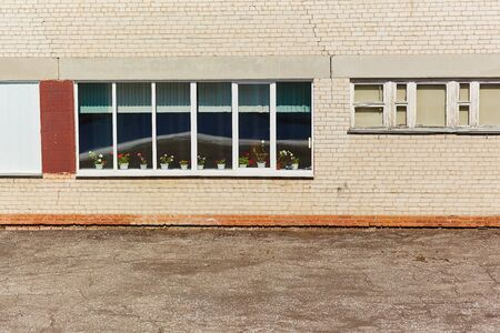 The wall of the old brick building, with a window with wooden frames, on the windowsill is blooming geranium.