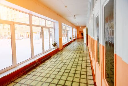 Perspective view of an old school or office building corridor , empty narrow, high and long , with many room doors and Windows. The interior design and the concept of education background