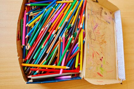 Lots of old colored wooden pencils in a cardboard box with childrens doodles. Reklamní fotografie