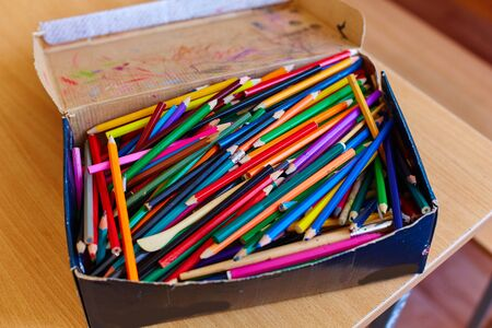 A lot of Old and broken colorful Pencils in cardboard box.