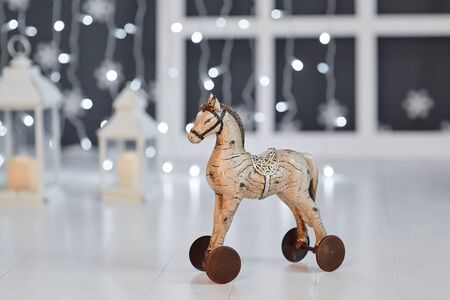 Toy wooden horse on wheels on the background of lights garland on a white wooden floor Reklamní fotografie