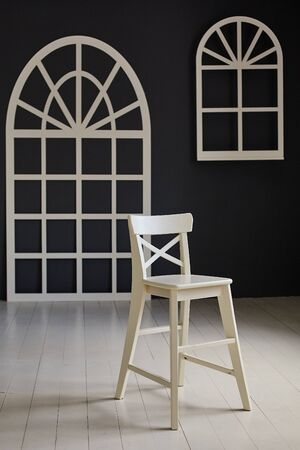 White chair on dark background. The wall is decorated with details in the form of arched doors and arched Windows Reklamní fotografie
