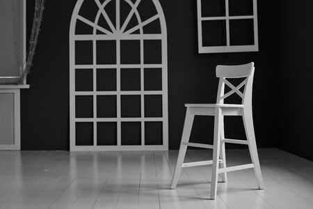 White chair on dark background. The wall is decorated with details in the form of arched doors and arched Windows