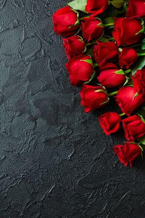 Red roses on a black textured background. Place for text, top view.