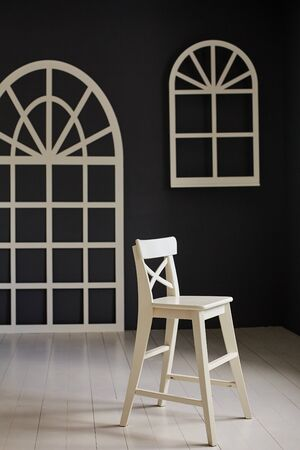 White chair on dark background. The wall is decorated with details in the form of arched doors and arched Windows Imagens