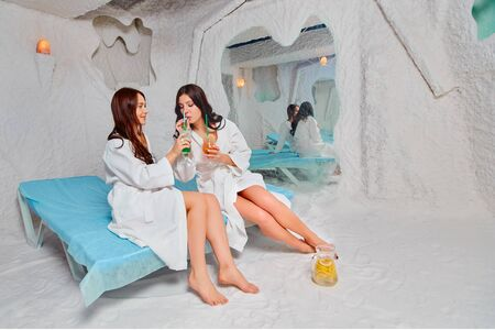 Two young women relax and drink a vitamin drink. Applying salt therapy in the Spa.