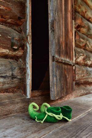 Fairy creature elf or forest dwarf left his shoes on the threshold of an old wooden house near the front door.