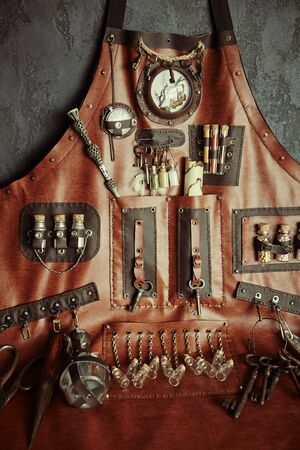 The concept of magic, witchcraft and alchemy. Apron with a set of items for witchcraft, making poisons and black magic.Composition of handmade and vintage items to designers. Historical simulation 写真素材