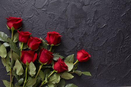 Red roses on a black, textured, stone background. Place for text, top view