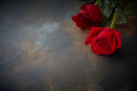 Red roses lie on a textured spotted marble background. A sign of condolence, sympathy for the loss. Space for your text Stock Photo