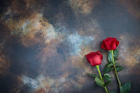 Red roses lie on a textured spotted marble background. A sign of condolence, sympathy for the loss. Space for your text 스톡 콘텐츠