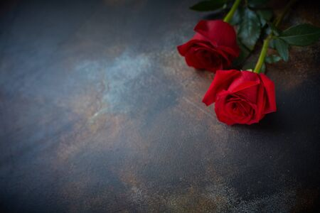 Red roses lie on a textured spotted marble background. A sign of condolence, sympathy for the loss.