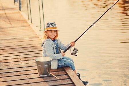 Cute child girl fishing from wooden pier on a lake. Family leisure activity during summer sunny day. little girl having fun by a river at beautiful summer evening. Active family time on nature.