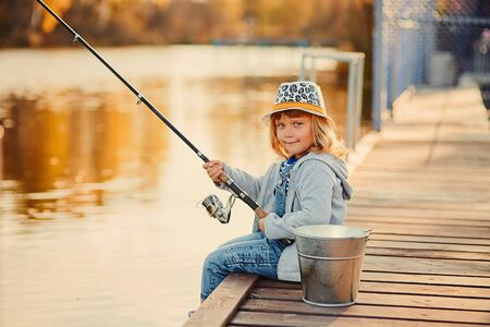 A little girl fishing with a fishing rod from a pontoon or pier on the pond fish farm.