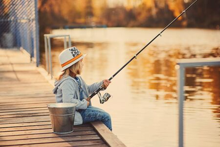 A little girl fishing from the pier on the pond in the Sunny morning