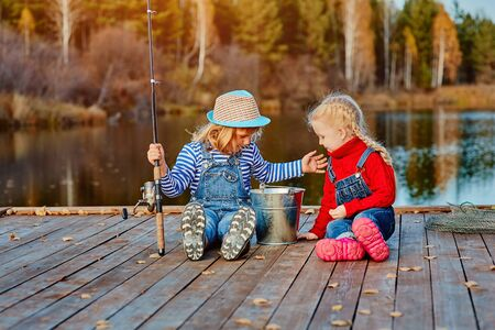 Two little sisters or friends sit with fishing rods on a wooden pier. They caught a fish and put it in a bucket. They are happy with their catch and discuss it