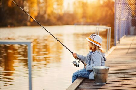 A little girl fishing from the pier on the pond in the Sunny morning.